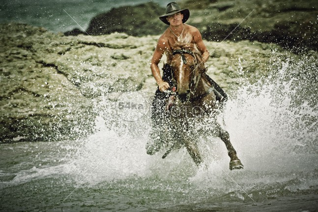 Man riding fast horse in the seawater young wild wet water trail tourism thoroughbred summer Standing stallion spring splashing speed sea satisfied saddle Running river rider ride Quick power pond outside outdoor ocean nature moving Motion mare man mammal landscape Lake journey horseman horseback horse gallop front freedom free equine equestrian domestic cowboy country brown beauty beautiful beach bathing animal action 54ka StockPhoto